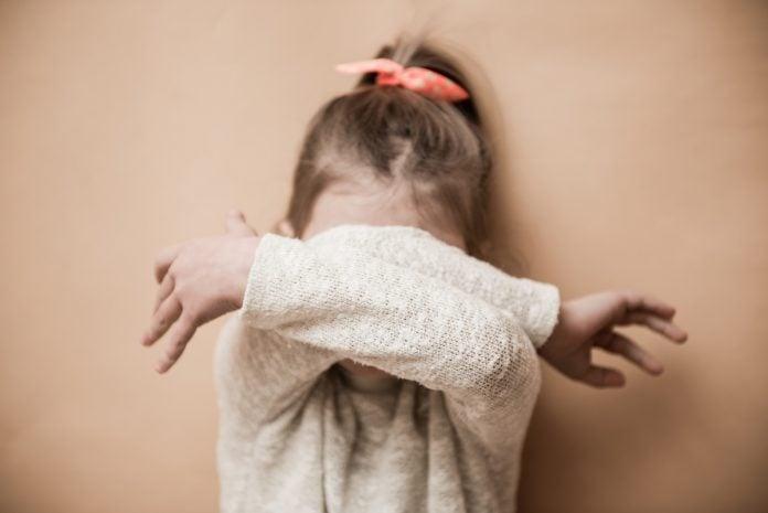 Crianças introvertidas na pandemia: saiba como ajudá-las; menina de cabelo preso cobre rosto com os braços