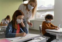 Piora da pandemia não tem relação com as escolas abertas; professora de máscara em pé fala com aluna de máscara sentada em carteira escolar