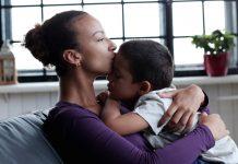 Você tem uma visão clara de onde sua família estará daqui a alguns anos?; mãe abraça menino que está em seu colo e beija sua testa, ambos sentados no sofá