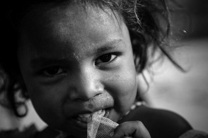 Crianças em situação de vulnerabilidade durante a pandemia; menina de trança morena está sentada e olha para o horizonte séria