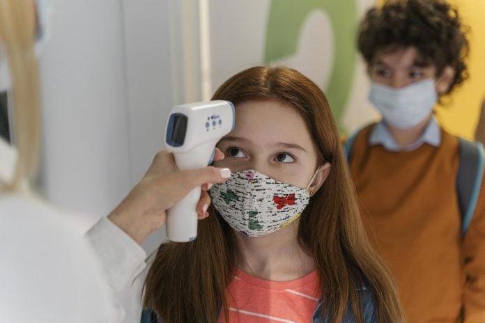 Reabertura das escolas particulares: 13 estados e o Distrito Federal retomam aulas presenciais; mão de adulto segura termômetro para aferir temperatura de menina de máscara
