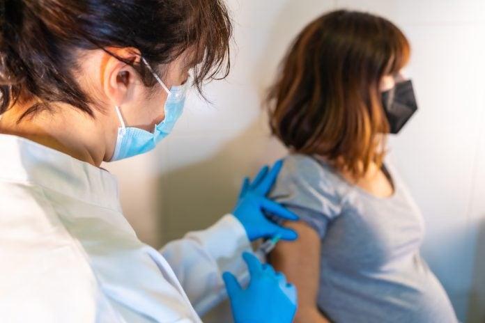 Grávidas e puérperas entram em grupo prioritário n % a vacina contra covid; mulher de bata branca e máscara vacina gestante