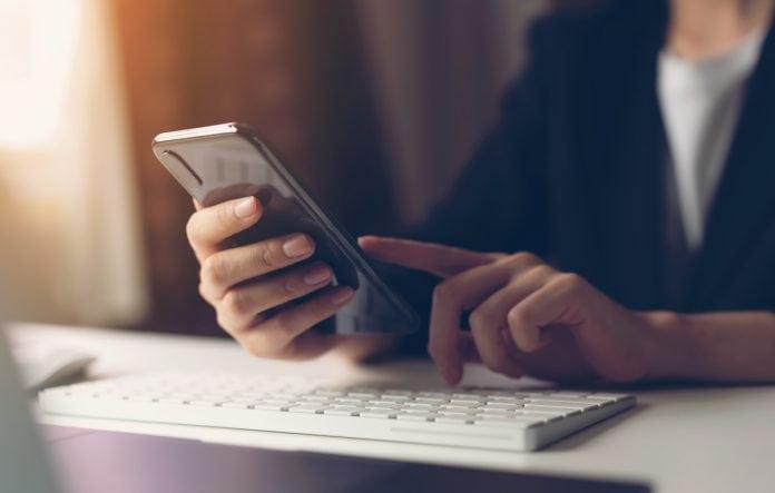 Retomada das aulas acirra brigas em grupos de pais no WhatsApp; mão segura celular e dedo toca na tela do aparelho