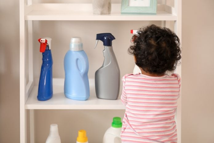 Aprenda como prevenir e proceder em caso de intoxicação de crianças; menino pequeno mexe em produtos de limpeza em prateleira de sua altura