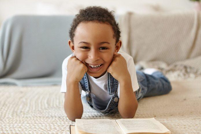 Estudo mostra impacto da pandemia em crianças da educação infantil; mãos de duas crianças e um adulto seguram pincéis em copo com água sobre mesa que tem também bolas de argila pintadas