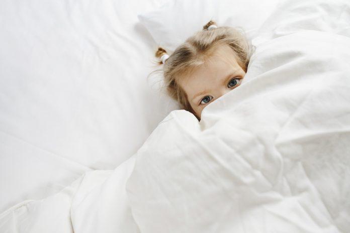 Masturbação infantil: como conversar sobre isso com os filhos; menina de olhos claros está deitada em cama coberta com lençol branco até os olhos
