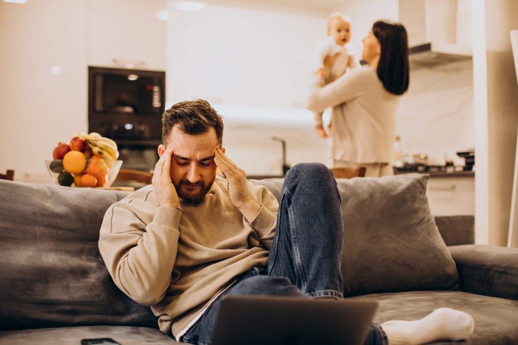 Pais exaustos: 3 atitudes para enfrentar o turbilhão; homem sentado no sofá com mãos na cabeça e mulher ao fundo em pé segura bebê nos braços