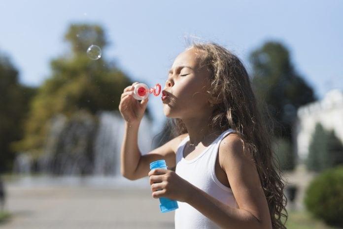 Poluição pode alterar genes de crianças e aumenta risco de doenças cardíacas; menina de cabelo grande brinca de soprar bolhas em espaço ao ar livre