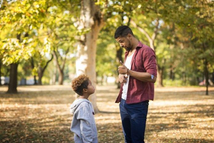 Filhos disciplinados: como chegar ao equilíbrio entre a punição e a permissividade; pai conversa com o filho em meio a parque ao ar livre faz sinal de 'joia' com a mão