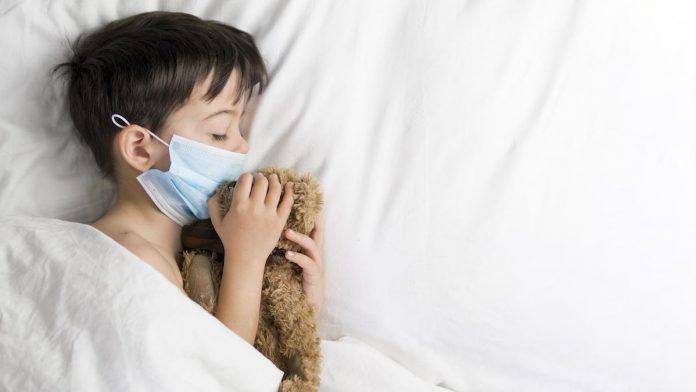 Síndrome pós-covid em crianças: saiba o que ela pode causar; menino dorme de máscara e segura ursinho de pelúcia nas mãos