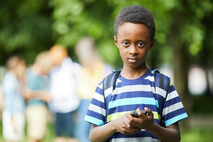 Exclusão escolar na pandemia afeta mais as crianças entre 6 e 10 anos; menino negro de mochila nas costas olha fixamente para a câmera
