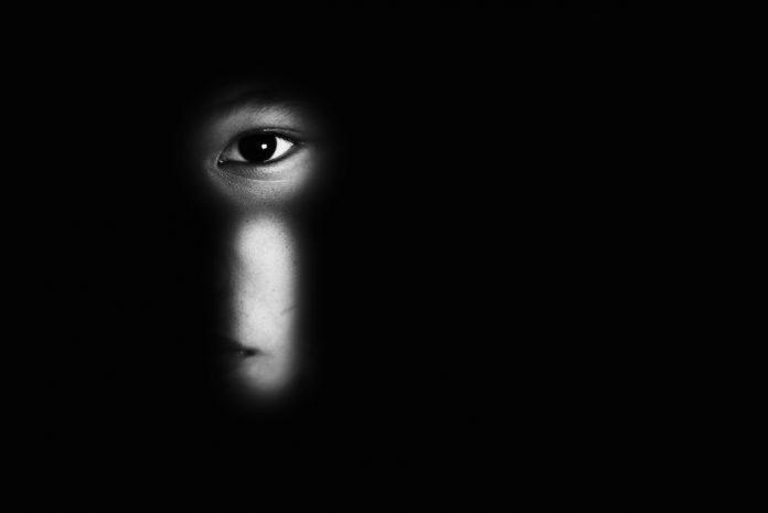 Violência contra criança: como identificar sinais de maus tratos; olho de criança é visto por meio de fechadura em imagem toda preta