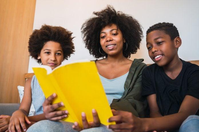 3 livros sobre ansiedade e solidão; mulher segurando um livro de capa amarela e lendo para duas crianças