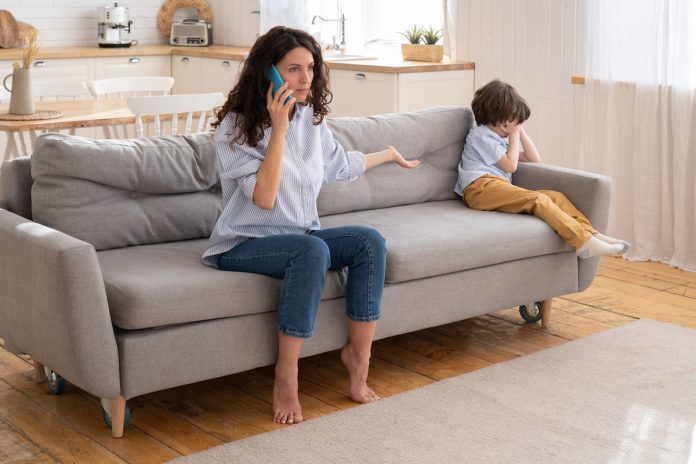 6 práticas comuns de alienação parental na pandemia; mãe sentada no sofá fala ao telefone e tem braço esticado para o lado com palma da mão para cima, n canto do sofá criança está sentada encolhida