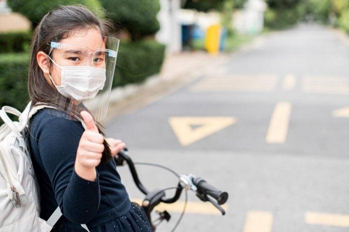 Liberdade sobre rodas: andar de bicicleta ganha mais relevância na pandemia; menina andando de bicicleta com máscara e face-shield