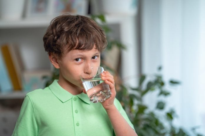 Qual o consumo de água diário indicado para crianças e adultos?; menino de blusa verde bebe água de um copo