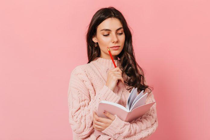 O autoconhecimento pode ajudar na sua relação com o seu filho; mãe pensativa segura lápis com uma mão, apoiado sobre queixo, e na outra mão segura um caderno aberto
