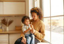 O desafio de usarmos emoções saudáveis ao educar os filhos; mãe está sentada em banda de janela com filho no colo