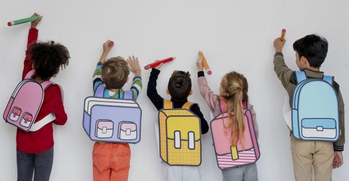 O aprendizado das crianças que acontece nos 'corredores', fora da sala de aula; 5 alunos de mochilas ilustradas na imagem desenham em quadro branco