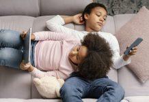 7 razões para que crianças não fiquem sozinhas na internet; menina de cabelo crespo está deitada sobre barriga de menino, ele segura e olha para celular, ela tem tablet nas mãos