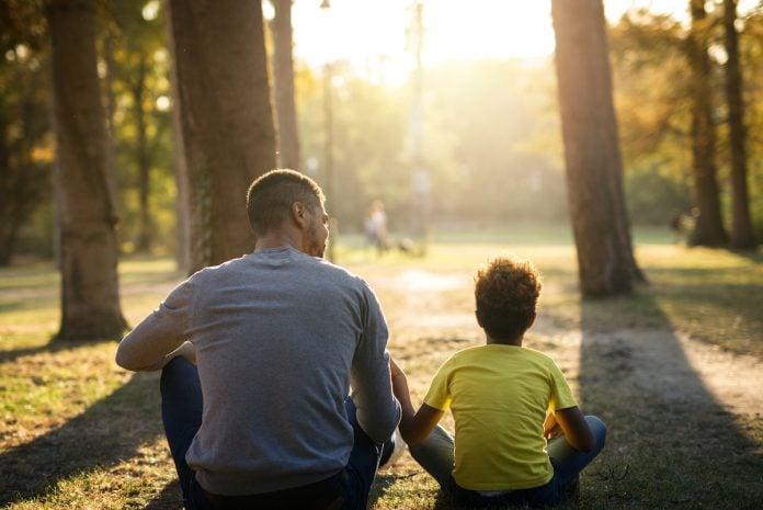 O silêncio, como resposta, pode ser útil para o filho; pai e filho estão em área verde, com árvores, sentados no chão de costas para a câmera