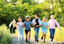 A busca pela saúde das crianças tem prescrição: mais contato com a natureza; 5 crianças caminham lado a lado em área verde ao ar livre
