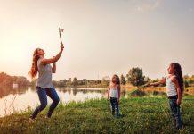 Muitos pais têm medo de errar com os filhos, mas isso faz parte da jornada; mulher rebate peteca com raquete e duas crianças olham para ela em área verde ao ar livre
