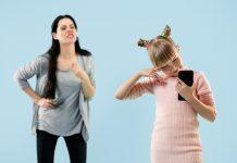 Não use a sua raiva para tentar controlar as crianças; mãe de cara feia fala para a filha que segura celular e dá as costas para a mãe