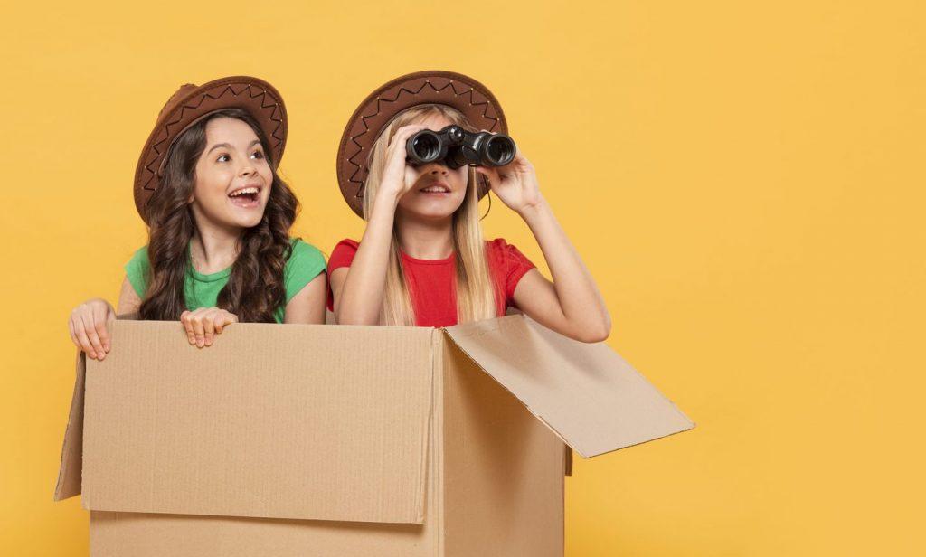 Os benefícios do brincar para o desenvolvimento da criança; duas meninas dentro de uma caixa brincando