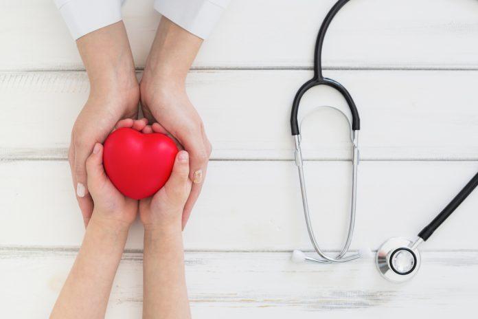 HCor oferece atendimentos gratuitos para crianças com cardiopatia; mãos de um adulto envolvem mãos de uma criança que tem um coração vermelho e do lado há um estetoscópio