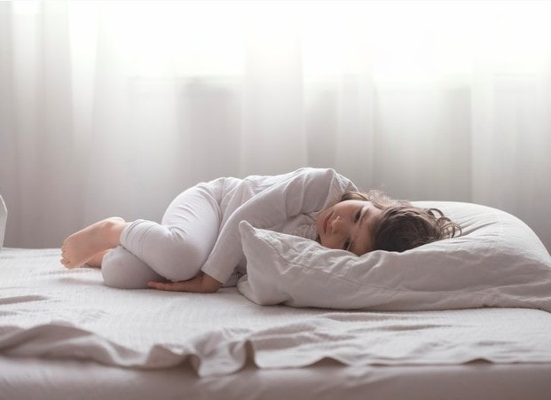 Distúrbios de sono de crianças autistas aumentam durante a pandemia; menina deitada na cama está encolhida e de olhos abertos