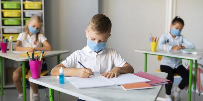 Escolas particulares perdem um terço das matrículas na pandemia; três alunos com máscaras sentados em carteiras escolares escrevem em cadernos