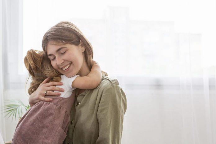 A importância de pedir desculpas ao filho; mulher feliz abraçando criança