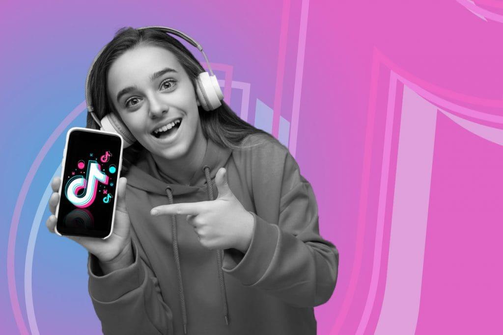 Crianças no TikTok: especialistas comentam riscos no uso do aplicativo; menina de fone d eouvido aponta para celular que segura na mão e tem símbolo do TikTok