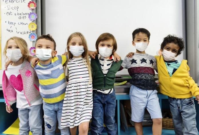 Estudo mostra que crianças têm mais chances de contrair a covid-19 do que de transmiti-la; crianças de máscara abraçadas olham para a câmera
