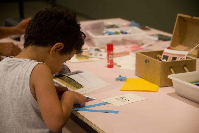 MAM oferece atividades educativas online em maio; criança de costas desenhando sobre mesa
