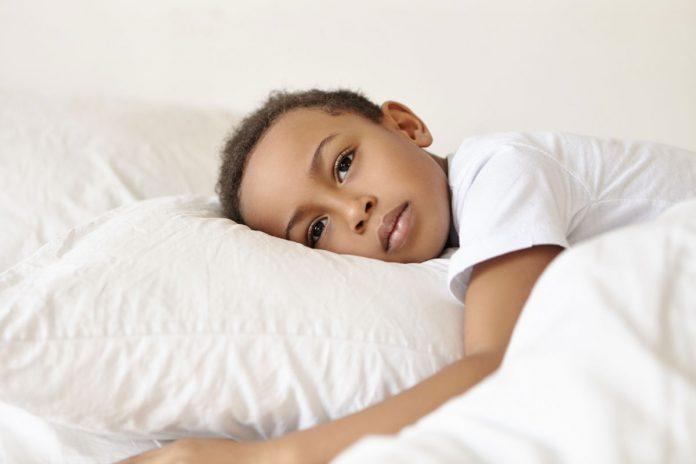 Enurese noturna: saiba como prevenir o xixi na cama durante o sono em crianças; menino moreno está deitado na cama com cabeça sobre travesseiro branco e olhos abertos com expressão séria