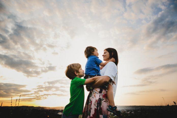 Assim como somos pais imperfeitos, temos filhos imperfeitos; mãe segura filho no colo enquanto outro garoto abraça o irmão e a mãe