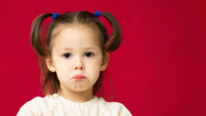 A humilhação e a vergonha na educação do filho; menina com franja presa nos dois lados faz bico com a boca em imagem de fundo vermelho