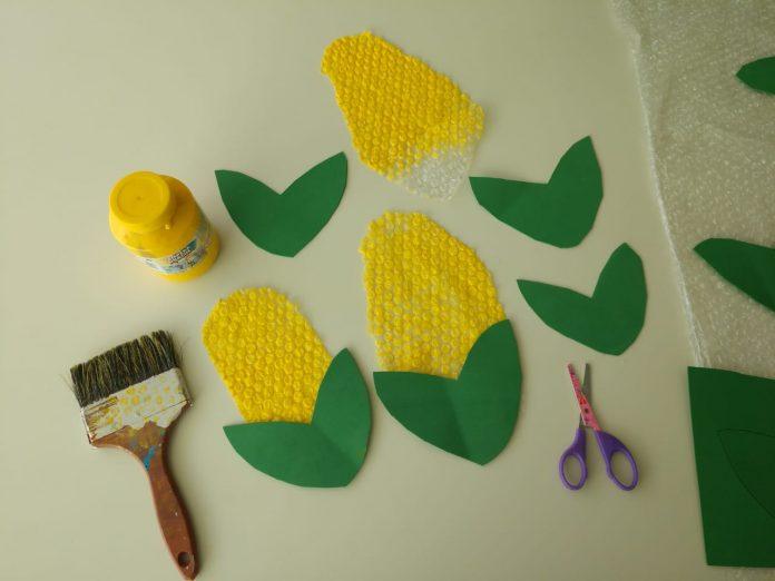 Decoração junina: convide as crianças a fazer milhos para enfeitar a casa; milho feito de plástico-bolha e cartolina verde, tesoura, pincel e tinta amarela