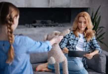 4 hábitos que prejudicam a comunicação com os filhos; mãe olha para tablet e filha se dirige a ela segurando bicho de pelúcia na mão