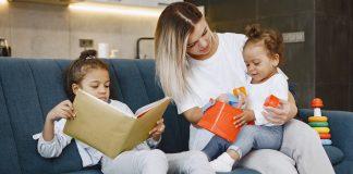 Crianças introvertidas vs extrovertidas: desafios na pandemia; uma criança lendo enquanto outra criança está brincando no colo da mãe