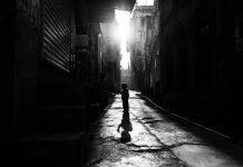 Os jabutis na árvore e os órfãos da Covid; criança anda em rua deserta e escura, foto em preto e branco