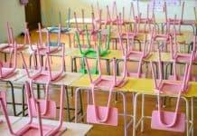 Os efeitos perversos da pandemia na educação; inúmeras cadeiras coloridas apoiadas sobre meses de sala de aula