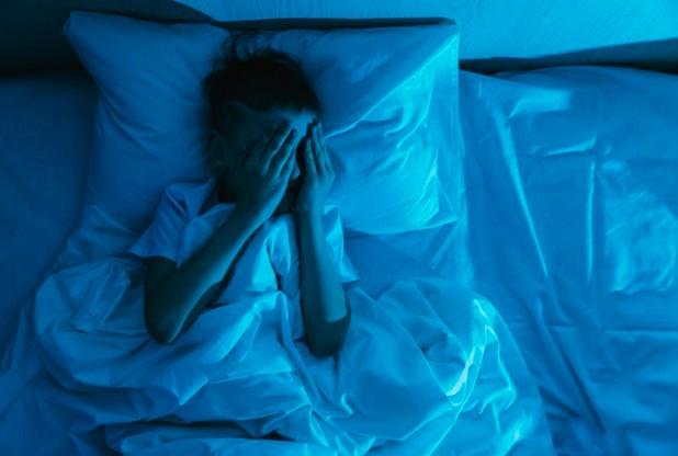 Os 4 distúrbios do sono que se agravaram na pandemia; menino deitado na cama em quarto escuro coloca mãos sobre rosto