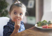 Mitos da alimentação infantil: deixe truques de lado e observe sinais do seu filho; menina de cabelo preso come tomate e tem prato à frente com tomate, brócolis e cenoura