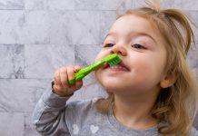 Os desafios de escovar bem os dentes das crianças; menina escova os dentes da frente com escova verde