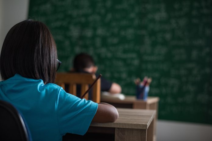 Escolha de diretores com critérios técnicos melhora ambiente escolar, diz estudo da FGV; aluno de costas escreve algo sobre banca escolar, lousa ao fundo