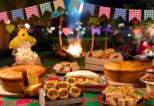 Festa junina virtual: dicas de brincadeiras para o arraial híbrido de 2021; comidas juninas, ao fundo bandeirinhas e fogueira