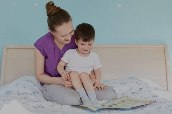 O que fazer para seu filho dormir sozinho no quarto dele (e a noite toda, de preferência); mãe lê para filho que está sentado em seu colo na cama